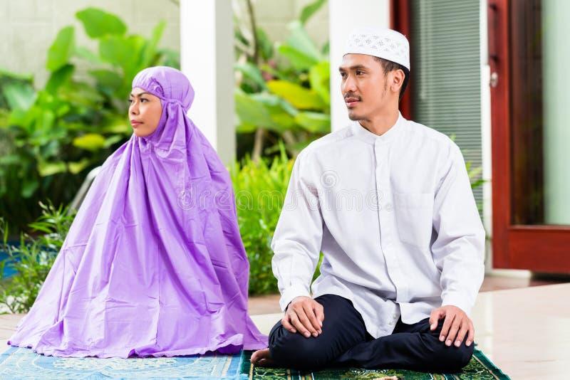 Asiatiska muslimska par, man och kvinna som hemma ber royaltyfria bilder