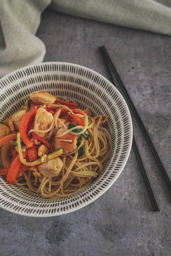 Asiatiska nudlar med grå kyckling och grönsaker arkivfoton