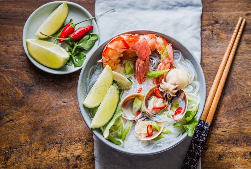 Asiatiska nudlar med räkor och skaldjur, kryddig soppa i bunke royaltyfri fotografi