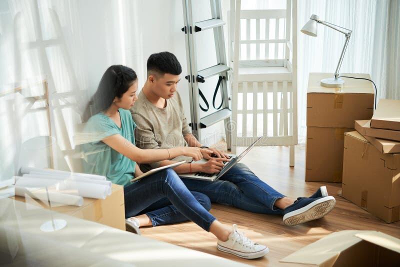 Asiatiska par genom att använda bärbara datorn under förflyttning arkivbild