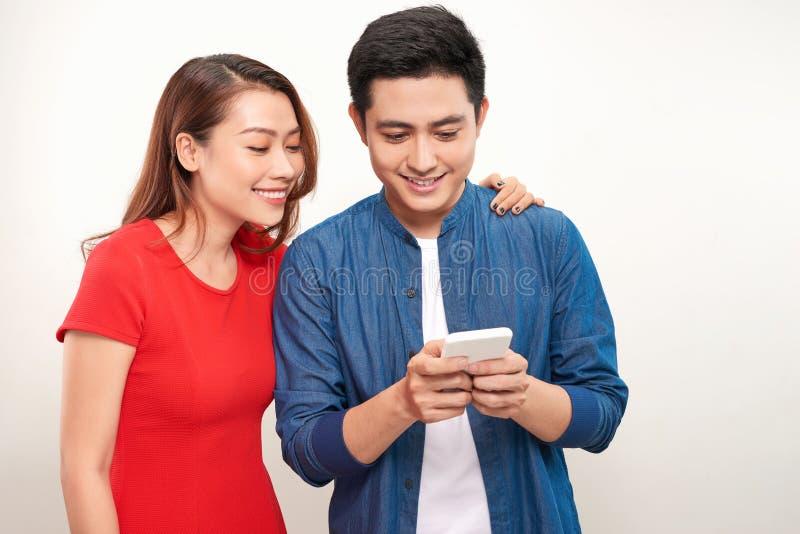 Asiatiska par genom att använda för telefonmeddelande för cell smart anseende för leende på vit bakgrund arkivbilder