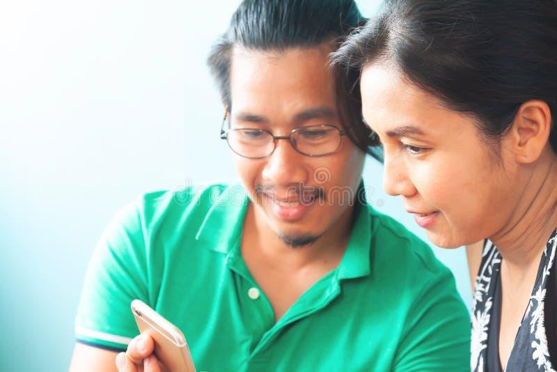 Asiatiska par genom att använda mobiltelefonen, fokus på att le kvinnan Lifesty fotografering för bildbyråer