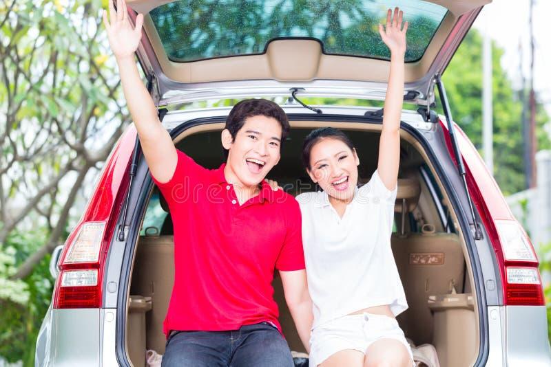 Asiatiska par med deras nya bil som är upphetsad arkivfoton