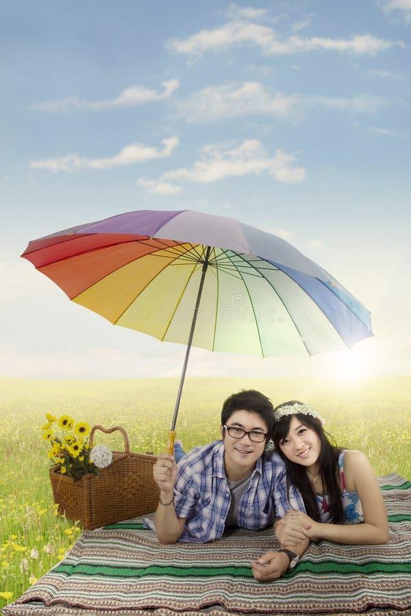 Asiatiska par med paraplyet i naturen fotografering för bildbyråer
