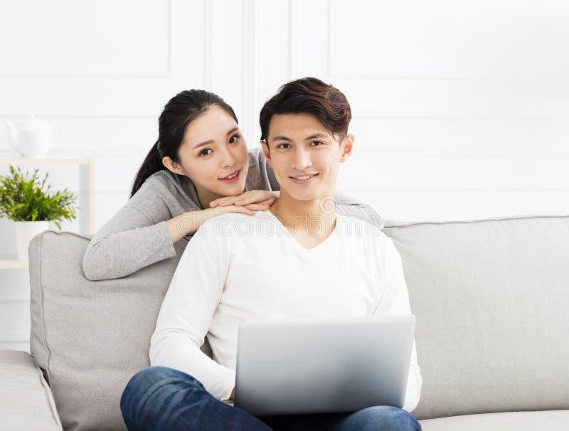 Asiatiska par på soffan med bärbara datorn royaltyfri foto