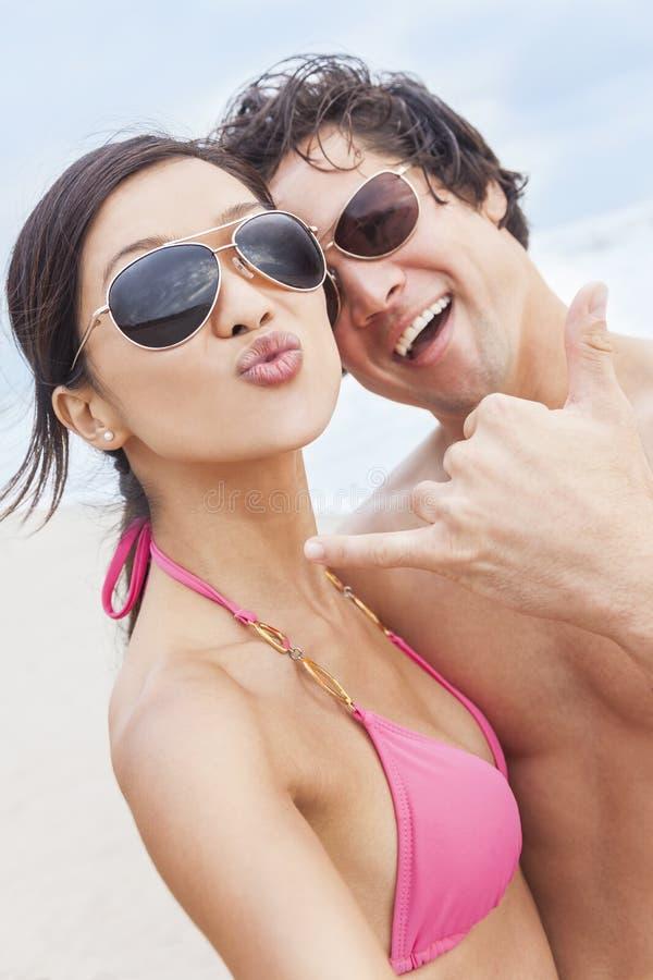 Asiatiska par på stranden som tar det Selfie fotografiet arkivfoton