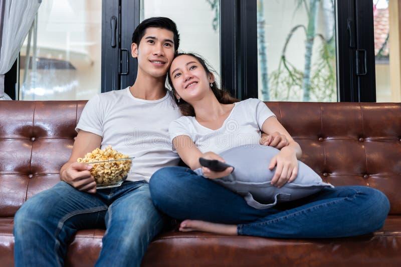 Asiatiska par som h?ller ?gonen p? television och tillsammans ?ter popcorn p? soffan i deras hem Folk och livsstilbegrepp Lycklig arkivfoto