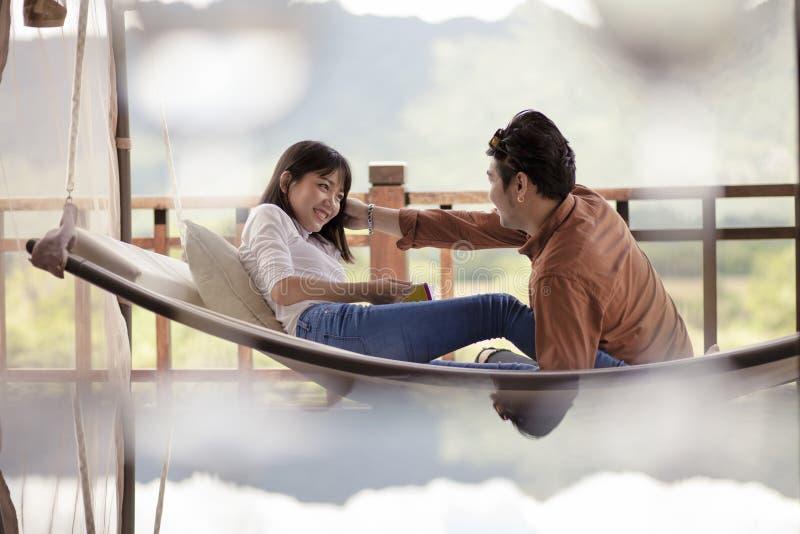 Asiatiska par som kopplar av semestertid på vagga royaltyfria foton