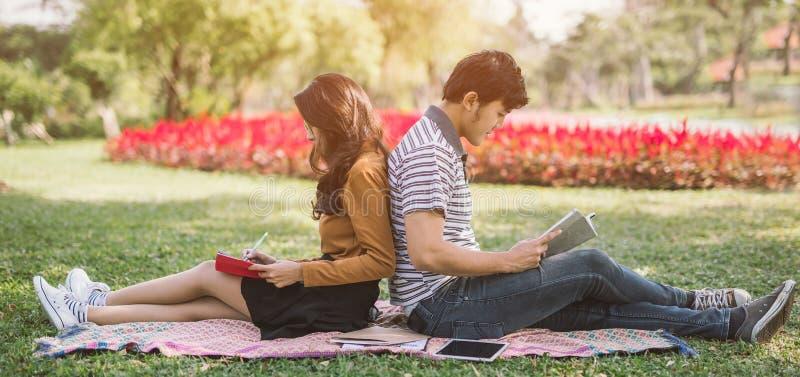 Asiatiska par som läser en bok Universitetsområdeliv Koppla ihop av studenter med böcker Utbildning i natur parkerar arkivfoton
