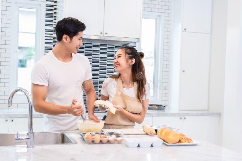 Asiatiska par som tillsammans lagar mat, och stekhet kaka i kökrum royaltyfri fotografi