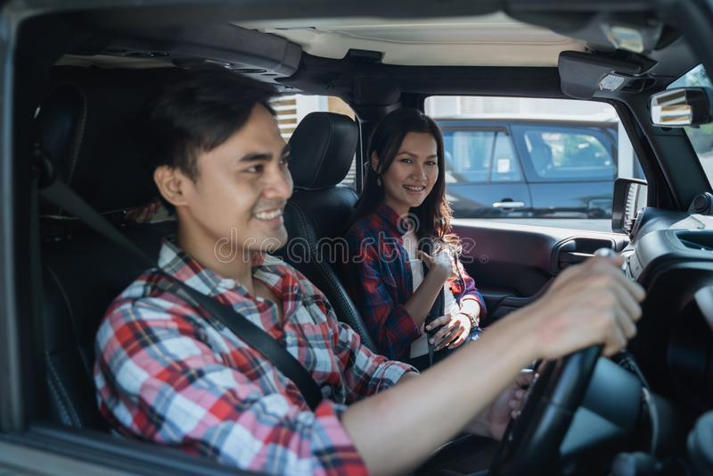 Asiatiska par som tillsammans passerar bilen royaltyfri bild