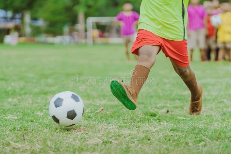 Asiatiska pojkar övar sparka bollen för att göra poäng mål fotografering för bildbyråer