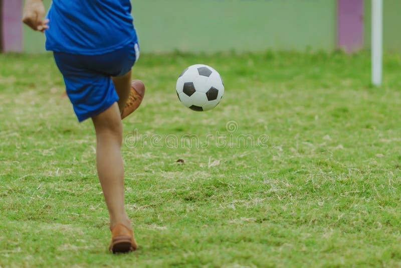 Asiatiska pojkar övar sparka bollen för att göra poäng mål royaltyfri foto