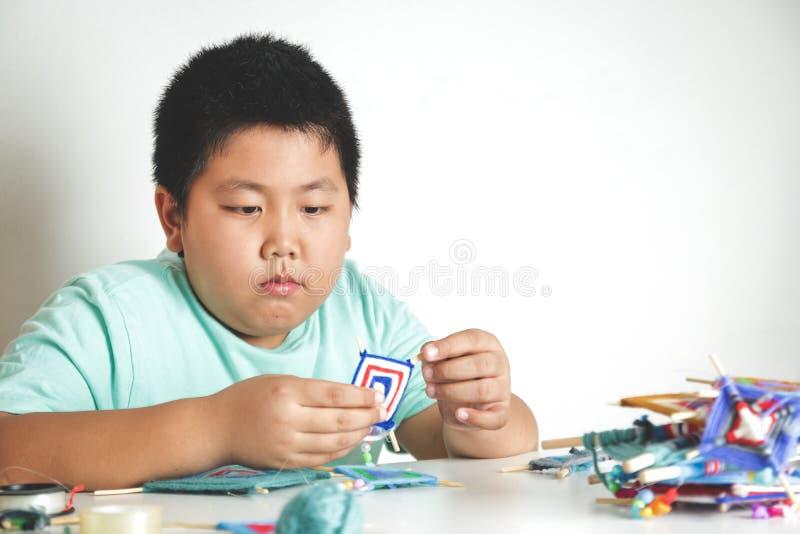 Asiatiska pojkar skapar leksaker som göras från handen fotografering för bildbyråer