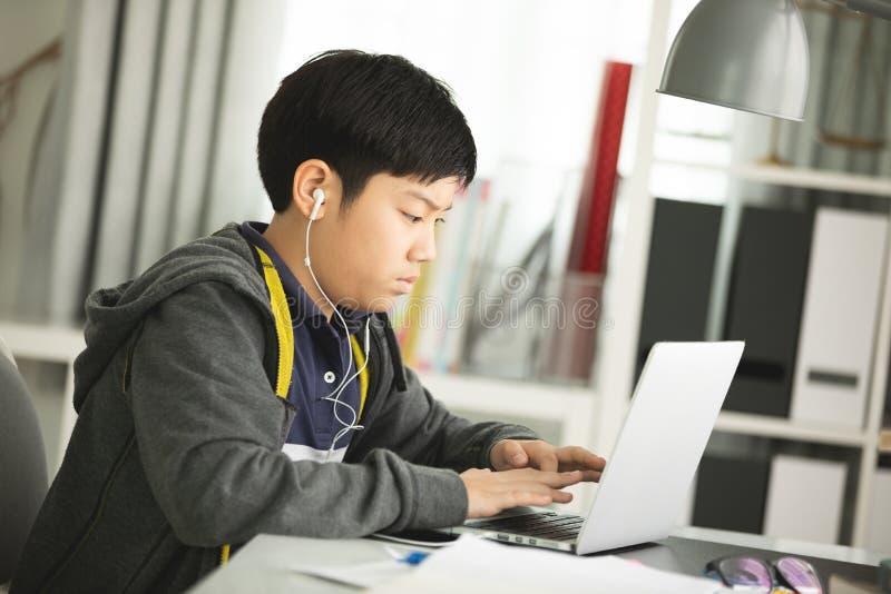 Asiatiska preteens som gör din läxa med bärbara datorn royaltyfri fotografi
