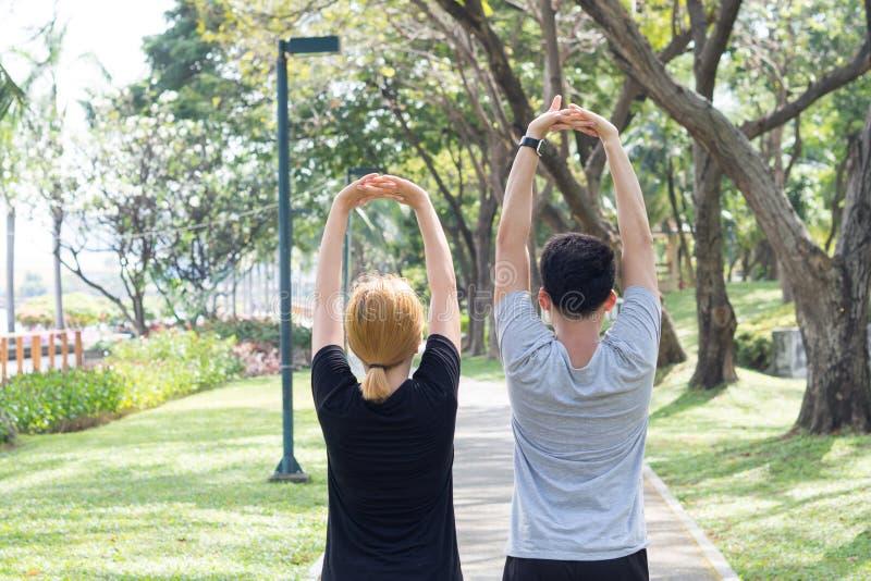 Asiatiska söta par värmer deras kroppar upp, genom att sträcka armar för jogga övning för morgon i parkera fotografering för bildbyråer