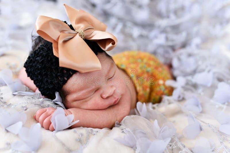 Asiatiska små behandla som ett barn den nyfödda flickan som sover på en snöra åt med blommamodellen fotografering för bildbyråer