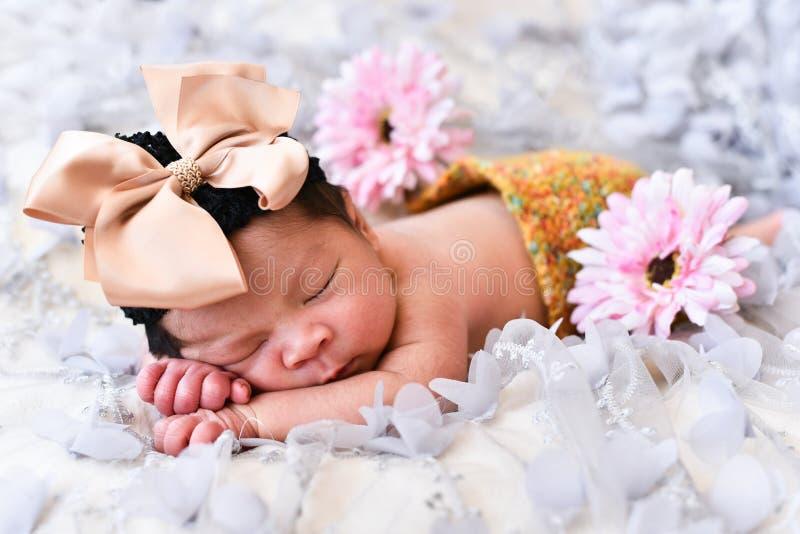 Asiatiska små behandla som ett barn den nyfödda flickan som sover på en snöra åt med blommamodellen royaltyfri foto