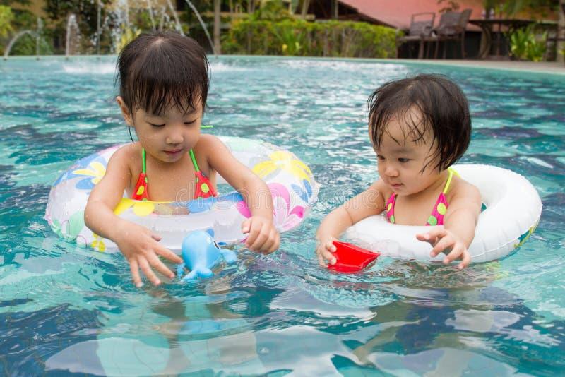 Asiatiska små kinesiska flickor som spelar i simbassäng arkivbild