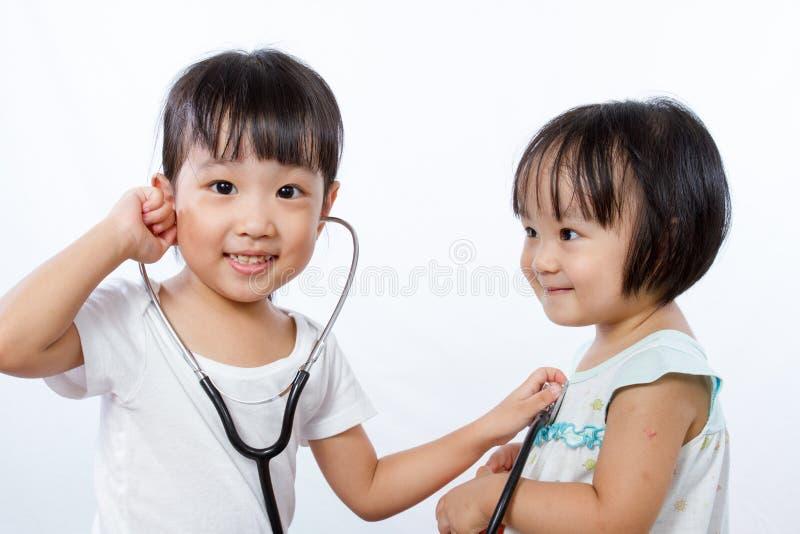 Asiatiska små kinesiska flickor som spelar som doktor och patient med St arkivbild