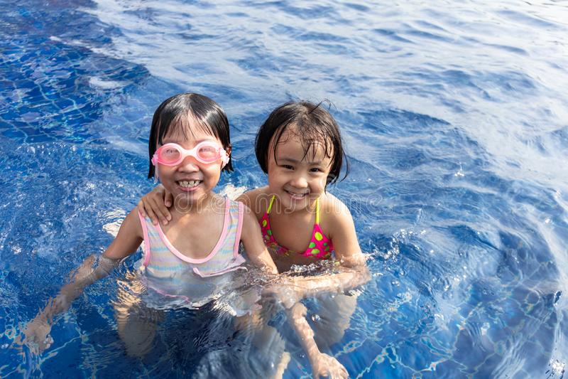 Asiatiska små kinesiska systrar som spelar i simbassäng arkivfoton