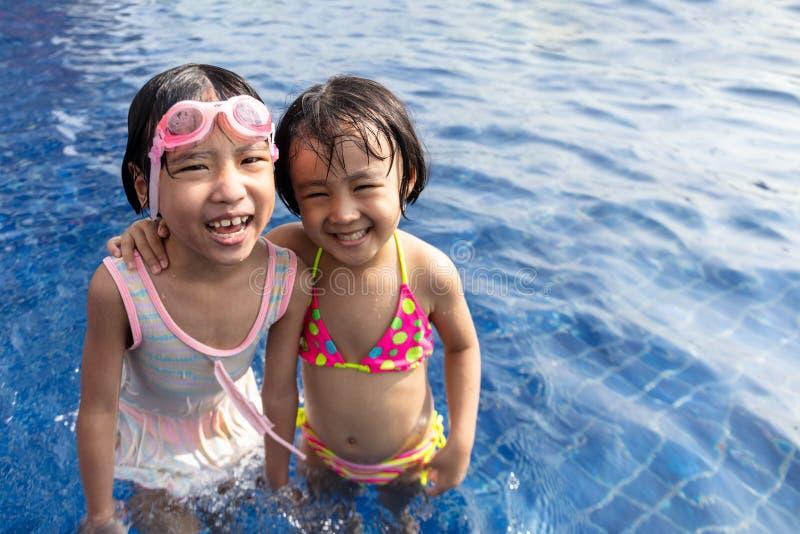 Asiatiska små kinesiska systrar som spelar i simbassäng royaltyfri fotografi