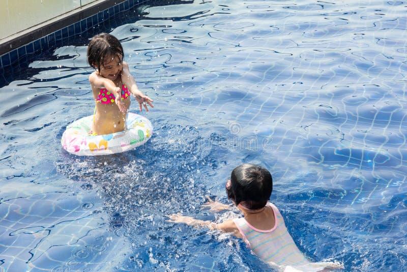 Asiatiska små kinesiska systrar som spelar i simbassäng royaltyfria foton