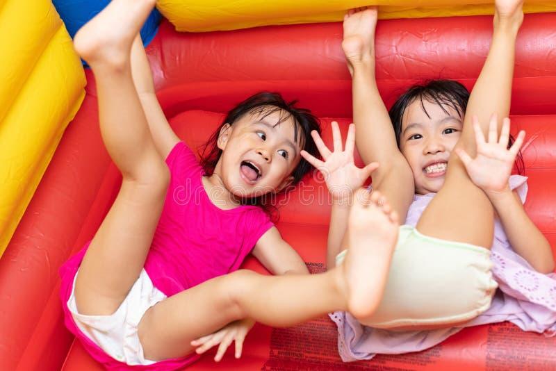 Asiatiska små kinesiska systrar som spelar på den uppblåsbara slotten royaltyfri fotografi