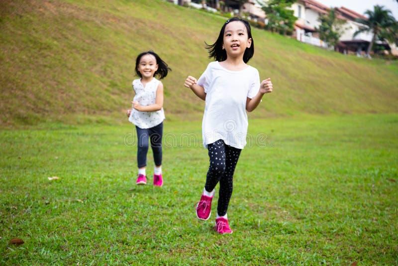 Asiatiska små kinesiska systrar springer lyckligt arkivfoton