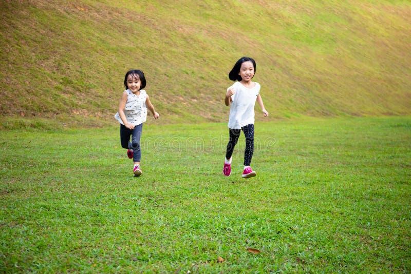 Asiatiska små kinesiska systrar springer lyckligt royaltyfri foto