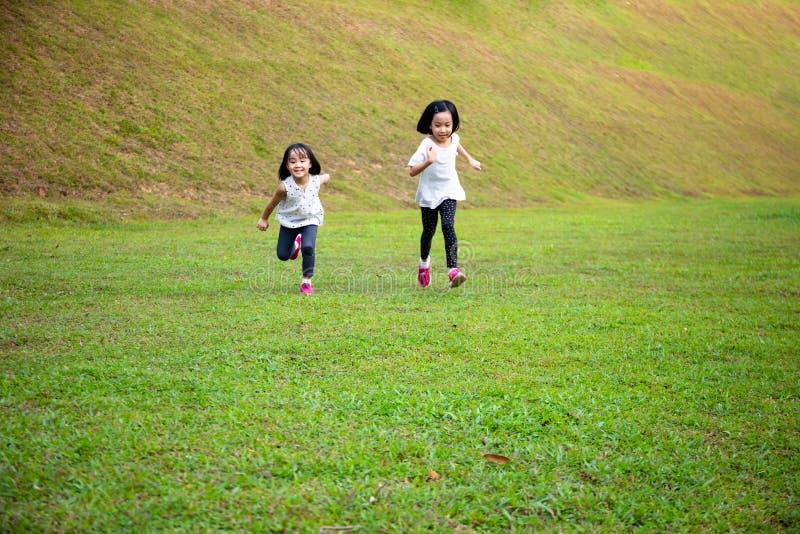 Asiatiska små kinesiska systrar springer lyckligt royaltyfri fotografi