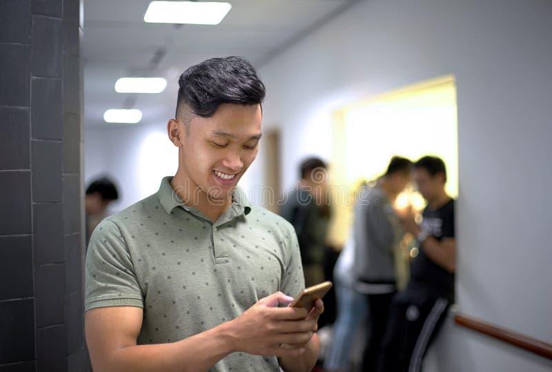 Asiatiska stiliga män som lyckligt talar på telefonen   Grabbleende, medan skriva meddelandesmartphonen royaltyfri foto