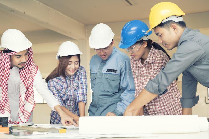 Asiatiska teknikerer konsulterades tillsammans och planerar i konstruktion royaltyfri bild