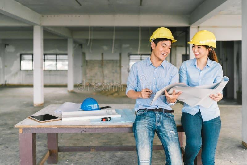 Asiatiska teknikerpar som tillsammans arbetar på byggnadsritning på den konstruktionsplatsen eller fabriken Begrepp för konstrukt royaltyfri foto