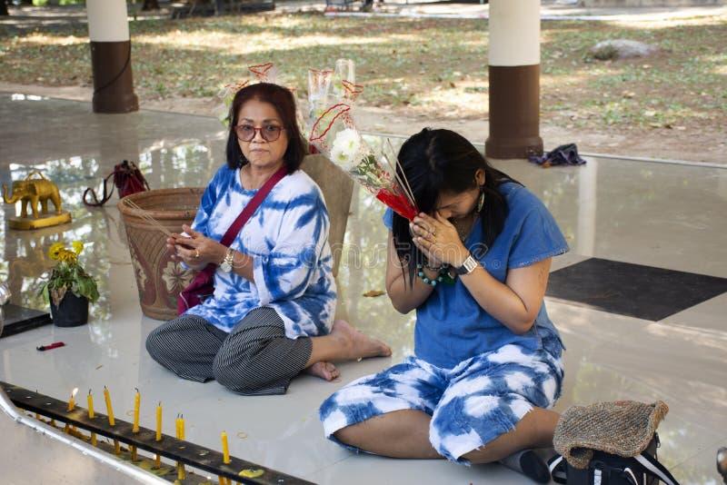 Asiatiska thai kvinnor moder och dotter sitter och respekterar att be den buddha statyn på Wat Phra That Doi Tung i Chiang Rai, T arkivfoton
