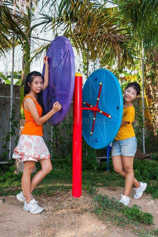 Asiatiska thailändska flickor med övningsmaskinen parkerar offentligt royaltyfria bilder