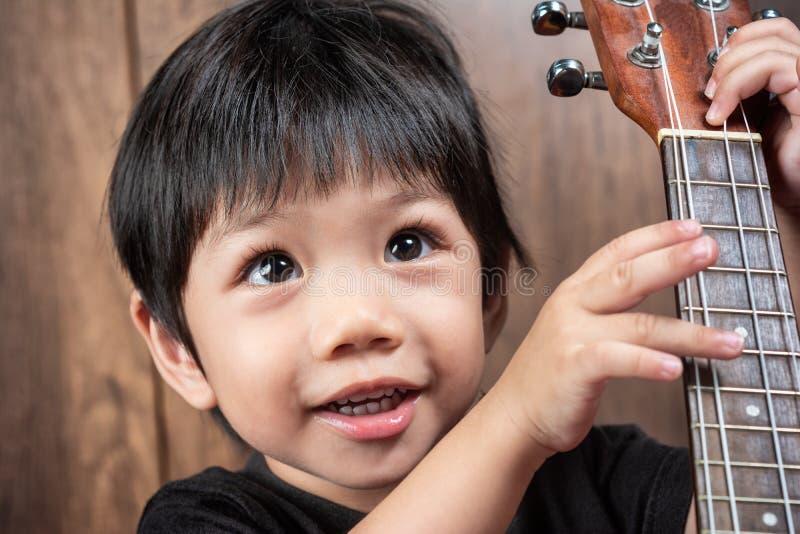 Asiatiska thailändska Little Boy som rymmer ukulelet i hand fotografering för bildbyråer