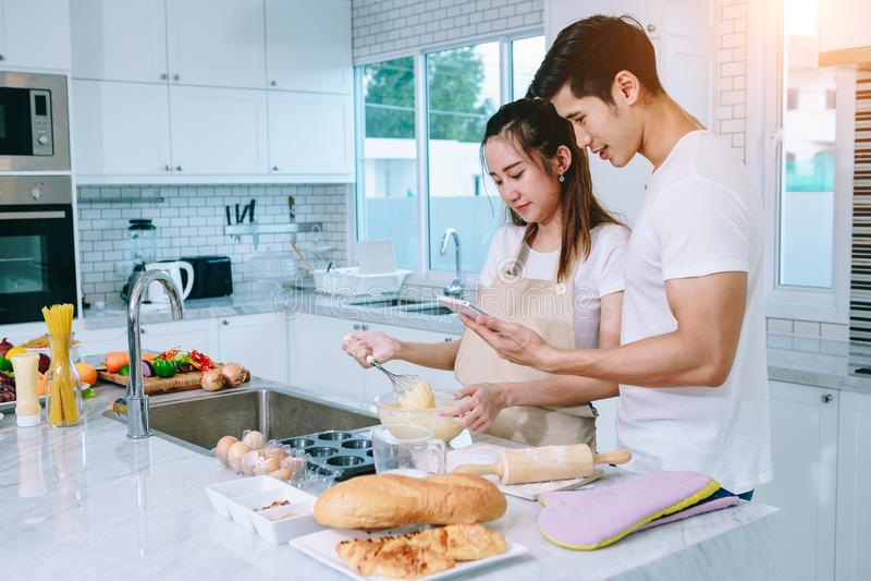 Asiatiska tonåriga par hjälper att göra matställen royaltyfri foto