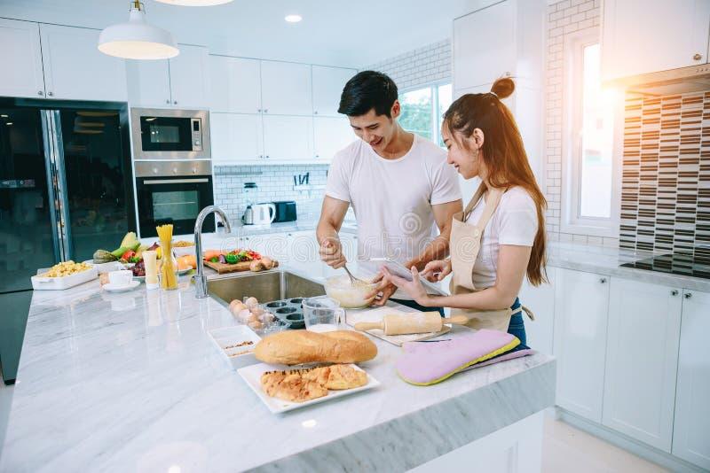 Asiatiska tonåriga par hjälper att göra matställen royaltyfri bild
