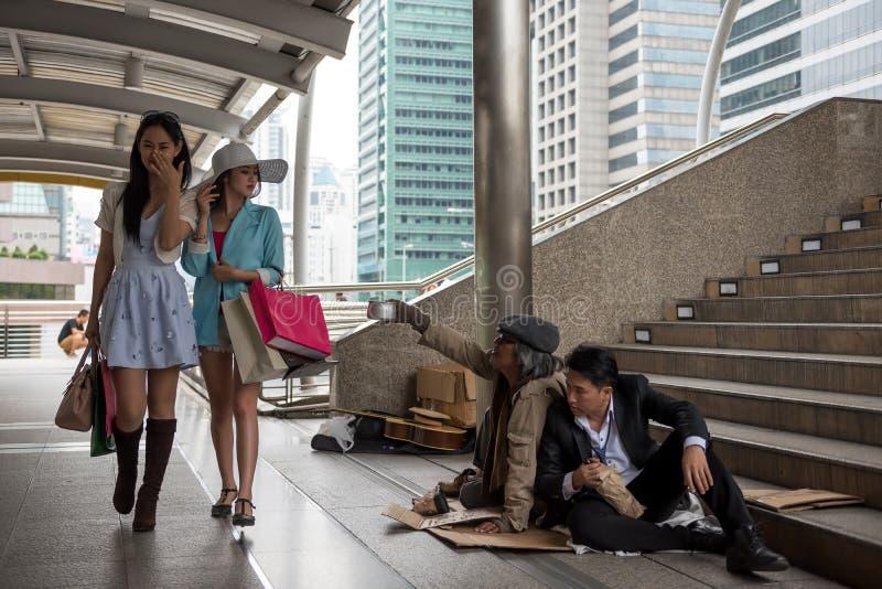 Asiatiska turist- kvinnor med många blick för shoppa påse ner på hemlös smutsig gammal grabb för lukt och berusad affärsman i sta arkivbild