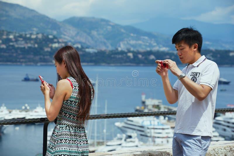 Asiatiska turister kontrollerar loppfoto på synvinkeln i Monaco royaltyfria bilder