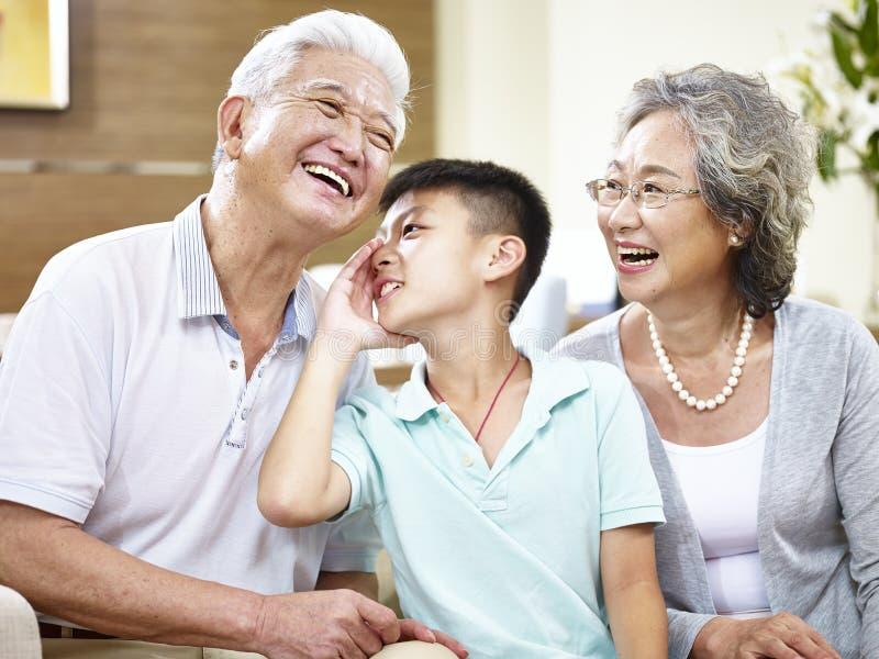 Asiatiska tusen dollarföräldrar och barnbarn som har gyckel arkivfoto