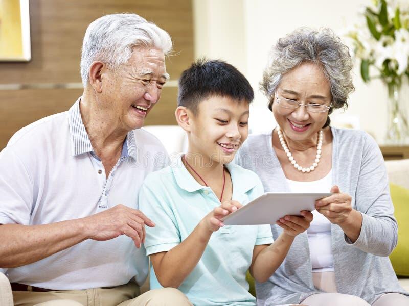 Asiatiska tusen dollarföräldrar och storslaget barn som hemma använder minnestavlan royaltyfria foton