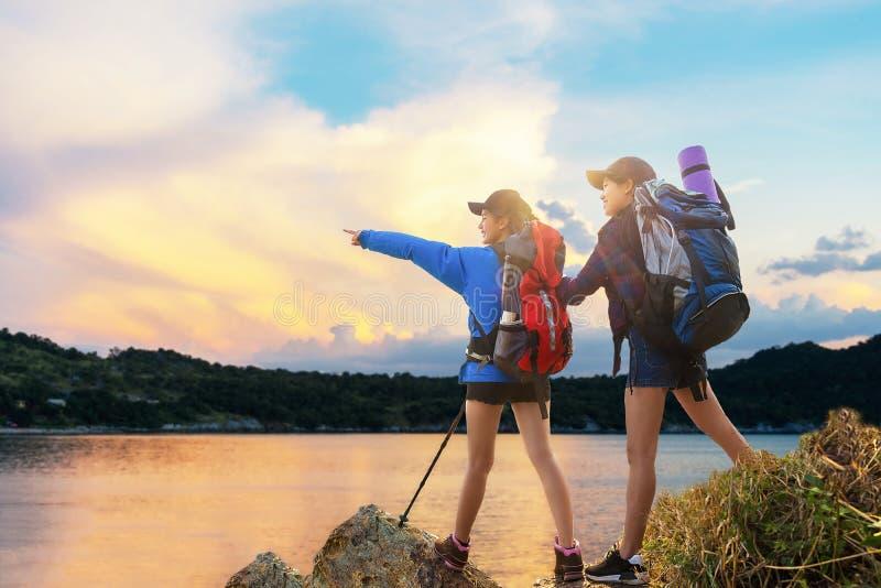 Asiatiska unga kvinnor för grupp av fotvandrare som går med ryggsäcken på ett berg på solnedgången Gående campa för handelsresand royaltyfria bilder
