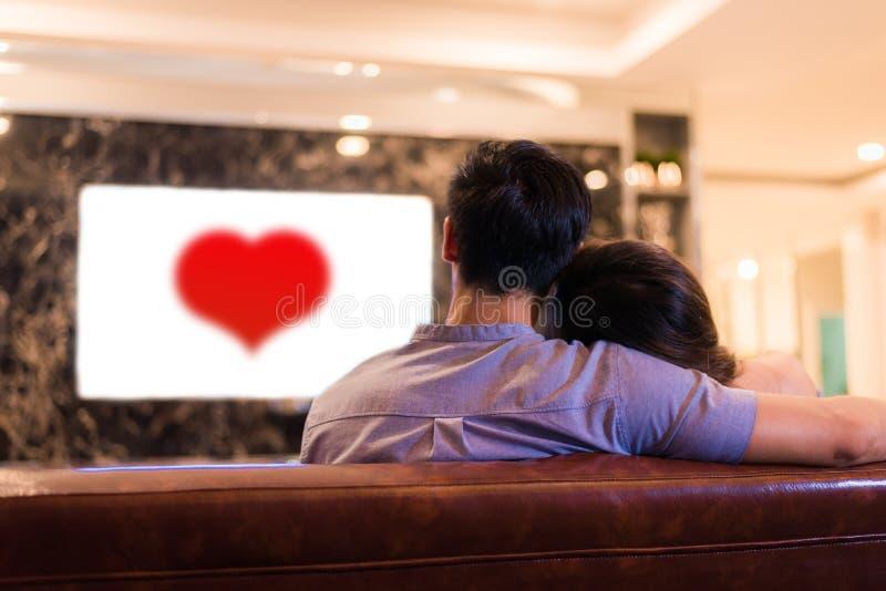 Asiatiska unga vänner som håller ögonen på television på soffan Par och verkligt royaltyfria bilder