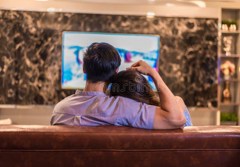 Asiatiska unga v?nner som h?ller ?gonen p? television p? soffan Par och kopplar av begrepp Ferie- och semesterbegrepp Natt som da royaltyfri fotografi