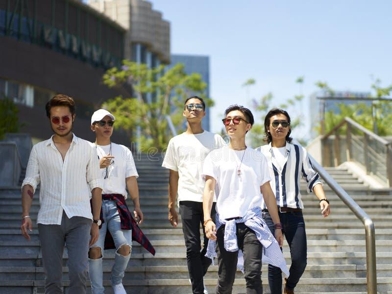 Asiatiska ungdomarsom går på gatan arkivfoton