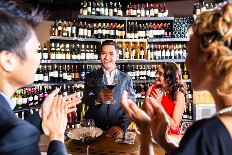 Asiatiska vänner som firar i restaurang royaltyfria bilder