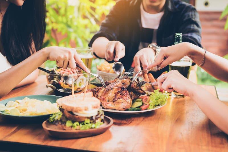 Asiatiska vänner som tycker om äta kalkon på restaurangen royaltyfri bild