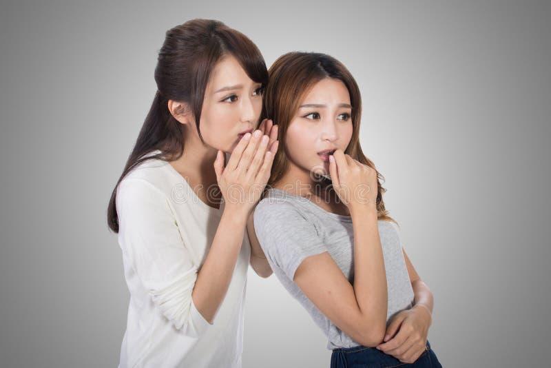 Asiatiska vänners viskning royaltyfri foto